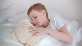 De zeven-jaar-oude jongen ontwaakte en strijkend een stuk speelgoed draag liggend in bed stock video