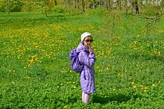 De zeven-jaar-oude meisjeskosten onder de tot bloei komende paardebloemen in het park De lente stock foto's