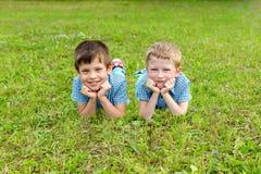 De zeven-jaar-oude tweelingen liggen op het gazon royalty-vrije stock foto