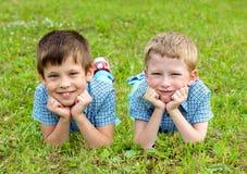 De zeven-jaar-oude tweelingen liggen op het gazon stock afbeeldingen