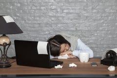 De zieke bedrijfsvrouw viel in slaap op het bureau met uitputting stock afbeeldingen