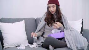 De zieke jonge Aziatische die vrouw voelt hoofdpijnzitting op een stoel in grijze deken in haar woonkamer thuis wordt verpakt stock videobeelden