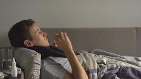 De zieke jonge mens blaast zijn neus in een zakdoek De de overvloedspillen en medicijnen zijn op de bedlijst stock video