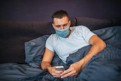 De zieke jonge mens ligt op bed en draagt masker Hij houdt telefoon in handen en bekijkt het De kerel is kalm en geconcentreerd royalty-vrije stock foto