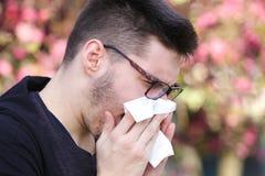 De zieke jongen met griep niest in het park royalty-vrije stock fotografie