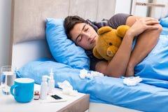 De zieke man met griep die in het bed liggen Stock Afbeelding