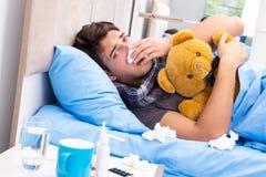 De zieke man met griep die in het bed liggen Stock Foto's
