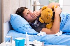 De zieke man met griep die in het bed liggen Stock Afbeeldingen