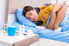 De zieke man met griep die in het bed liggen Royalty-vrije Stock Foto