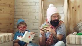De zieke mens in een GLB en een sjaal drinkt thee, en een jongen in een medisch uniform geeft hem geneeskunde van een eerste hulp stock videobeelden