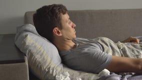 De zieke mens ligt in zijn bed en blaast zijn neus in een zakdoek stock video