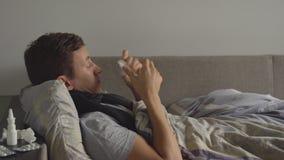 De zieke mens ligt in zijn bed en blaast zijn neus in een zakdoek De de overvloedspillen en medicijnen zijn op het bed stock videobeelden