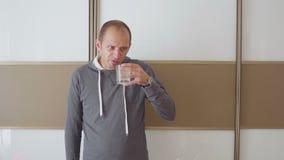 De zieke mensenhoest, blaast zijn neus en drinkt geneeskunde stock video