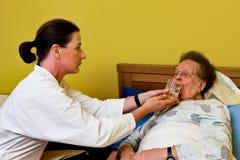 De zieke oude vrouw wordt bezocht Royalty-vrije Stock Afbeelding