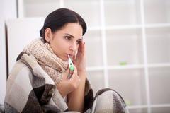 De zieke vrouw in bed met thermometer heeft /fe op hoge temperatuur Royalty-vrije Stock Foto