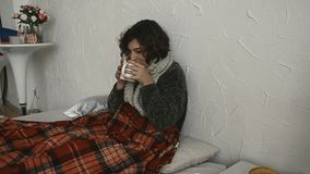De zieke vrouw ligt in bed in een sweater met een hete drank stock videobeelden