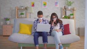 De zieken van koude jonge sian koppelen zitting in beschermende medische maskers op de laag en gebruiken laptop stock videobeelden