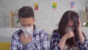 De zieken van koude jonge sian koppelen zitting in beschermende medische maskers op de laag stock videobeelden