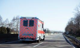 De ziekenwagen van Deutschesrotes Kreuz op Duitse landelijke weg stock afbeelding