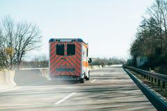 De ziekenwagen van Deutschesrotes Kreuz op Duitse landelijke weg stock foto