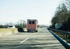 De ziekenwagen van Deutschesrotes Kreuz op Duitse landelijke weg stock afbeeldingen