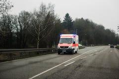 De ziekenwagen van Deutschesrotes Kreuz op een regenachtige dag stock foto