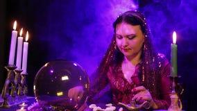 De zigeuner in een rode kleding in de rook door kaarslicht leest de toekomst in de stenen stock video