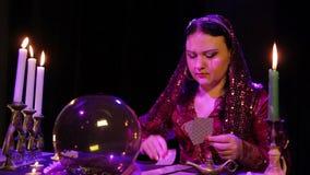 De zigeuner in een rode kleding in de rook door kaarslicht zet kaarten stock video