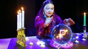 De zigeuner in de magichsky salon is bij de kristallen bol benieuwd en het roebelteken verschijnt daarin stock video