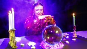 De zigeuner in de magische salon is bezig geweest met magisch met een kristallen bol, waarvan het brandteken van Bitcoin verschij stock videobeelden