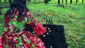 De zigeuner shuvany in het bos maakt magische bewegingen met overhandigt brandende kaarsen en witte kiezelstenen algemeen plan stock footage