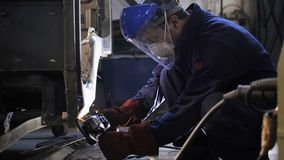 De zijaanzichtarbeider maalt vrachtwagencabine met handhulpmiddel stock videobeelden