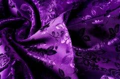 de zijde donkere sering van de achtergrondtextuurstof met een patroon met Th Royalty-vrije Stock Fotografie
