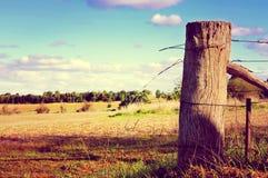 De zijscène van het land met oude poortpost en weerhaakdraad Royalty-vrije Stock Afbeelding