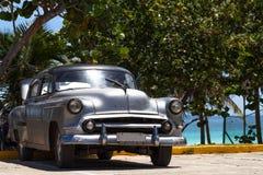 De zilveren Amerikaanse klassieke die auto van Cuba dichtbij het strand wordt geparkeerd Stock Fotografie