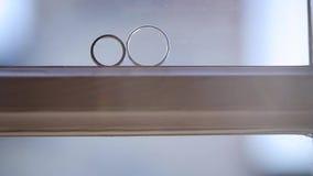 De zilveren bruiloftringen op het venster met lichte gloed macroclose-up schieten diamon Juwelen stock videobeelden