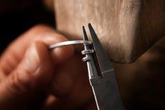 De zilveren draad van de goudsmidomslag met buigtang in een spiraal voor kleine cha royalty-vrije stock fotografie