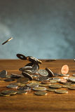 De zilveren en gouden muntstukken en dalende muntstukken op houten achtergrond Royalty-vrije Stock Foto