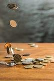 De zilveren en gouden muntstukken en dalende muntstukken op houten achtergrond Royalty-vrije Stock Afbeelding