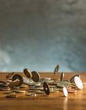 De zilveren en gouden muntstukken en dalende muntstukken op houten achtergrond Stock Fotografie