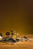 De zilveren en gouden muntstukken en dalende muntstukken op houten achtergrond Royalty-vrije Stock Foto's