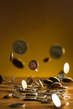 De zilveren en gouden muntstukken en dalende muntstukken op houten achtergrond Stock Foto's