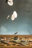 De zilveren en gouden muntstukken en dalende muntstukken op houten achtergrond Stock Afbeeldingen