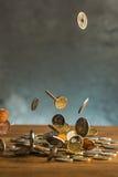 De zilveren en gouden muntstukken en dalende muntstukken op houten achtergrond Stock Foto