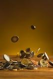 De zilveren en gouden muntstukken en dalende muntstukken op houten achtergrond Royalty-vrije Stock Afbeeldingen