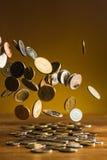 De zilveren en gouden muntstukken en dalende muntstukken op houten achtergrond Stock Afbeelding