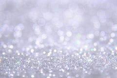 De zilveren en witte bokehlichten defocused abstracte achtergrond Stock Foto