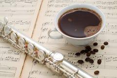 De zilveren fluit, de kop van koffie en de koffiebonen op een oude muziek noteren Stock Foto's