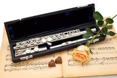 De zilveren gele fluit, namen en de chocoladeharten op een oude muziekscore toe Stock Fotografie