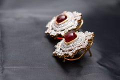 De zilveren met de hand gemaakte premieoorring met een rode robijn en het goud eindigen Royalty-vrije Stock Fotografie
